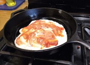 Rolled out dough in skillet with cashew cream and tomato paste spread on it